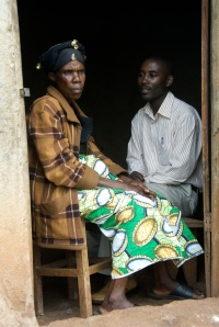 Simon Nsabiyeze, CAFOD's programme officer in Rwanda, talks to a woman in Musha