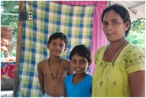 Existine and her children in the shelter they live in.