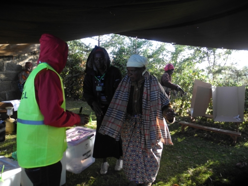 Mrs Lucia Nyamunyu Kabiru, a mother of 10, aged  70, ( right) is assisted by polling officials to cast her ballot at Kadenye polling centre, in Molo, in the Rift Valley.