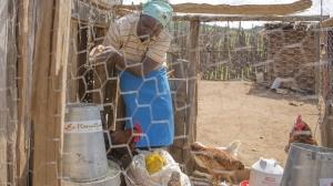 Kenya, Naomi feeds her chickens